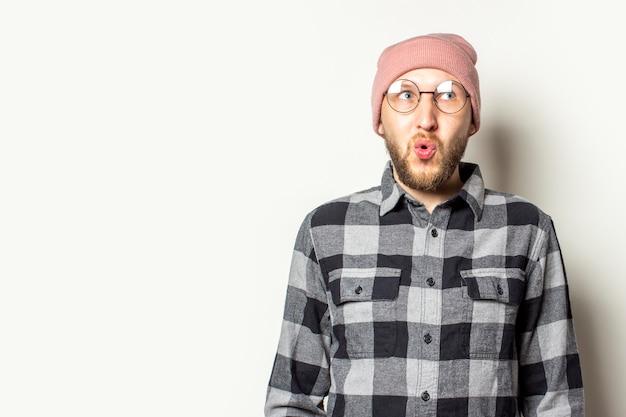 Junger mann mit bart in hut, kariertem hemd und brille schaut zur seite mit einem überraschten gesicht auf einem isolierten weiß.