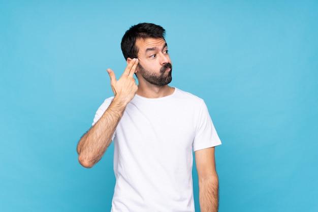 Junger mann mit bart über blau mit den problemen, die selbstmord machen, gestikulieren
