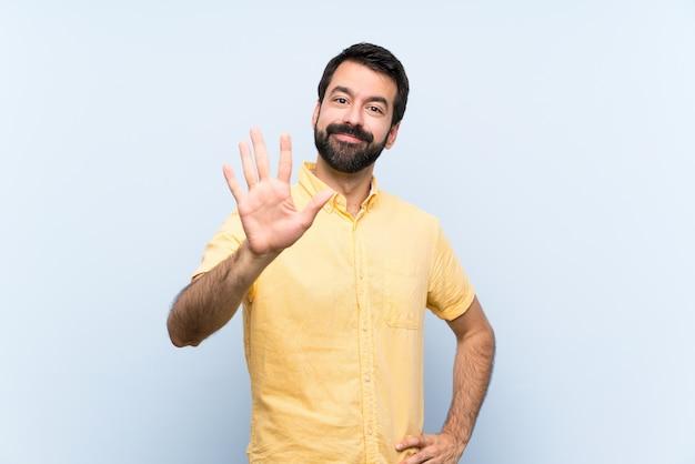 Junger mann mit bart über dem lokalisierten blau, das fünf mit den fingern zählt