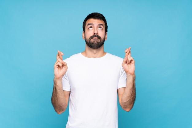 Junger mann mit bart über getrenntem blau mit den fingern, die das beste kreuzen und wünschen
