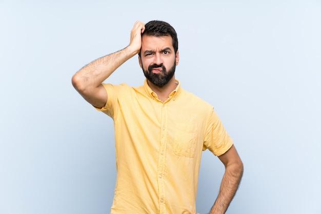 Junger mann mit bart über getrenntem blau mit einem ausdruck der frustration und des nichtverständnisses