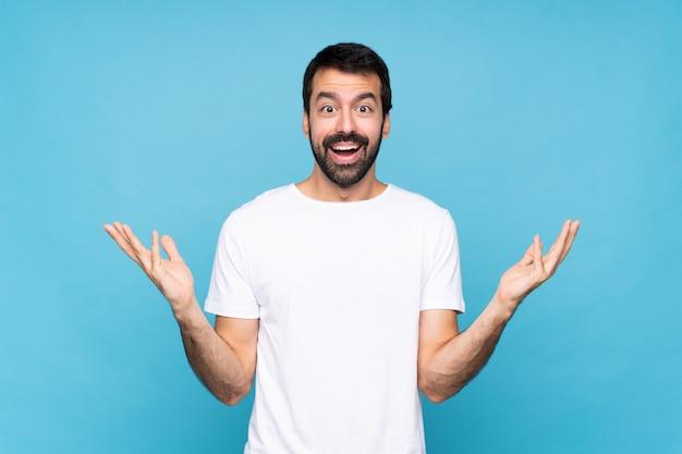 Junger mann mit bart über getrenntem blau mit entsetztem gesichtsausdruck