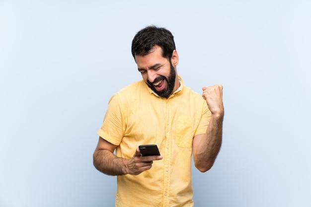 Junger mann mit bart über getrenntem blau mit telefon in siegstellung