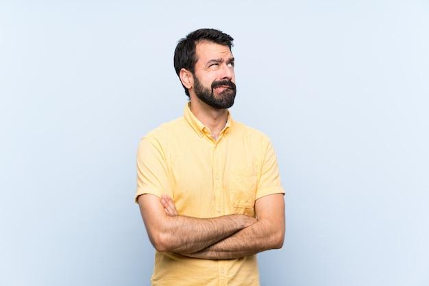Junger mann mit bart über getrenntem blau mit verwirren gesichtsausdruck