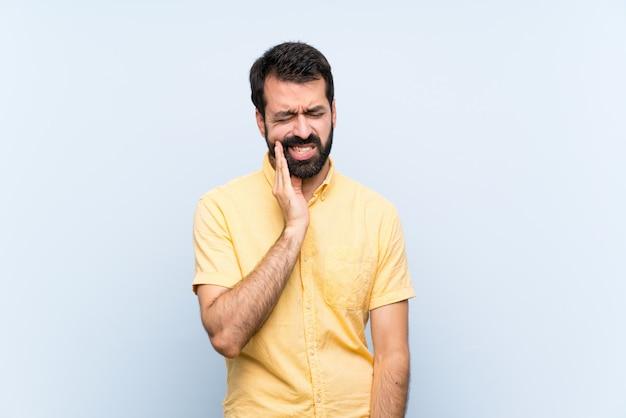 Junger mann mit bart über getrenntem blau mit zahnschmerzen