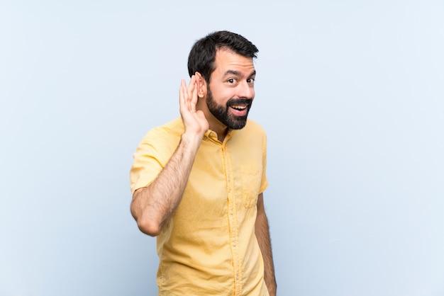 Junger mann mit bart über lokalisiertem blau hörend auf etwas, indem sie hand auf das ohr setzen