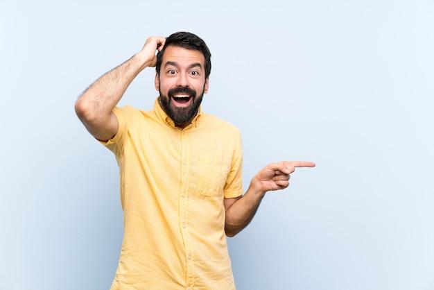 Junger mann mit bart über lokalisiertem blau überraschte und finger auf die seite zeigend