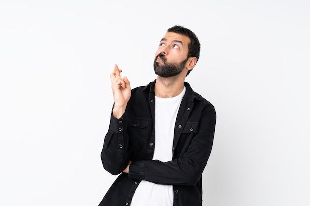 Junger mann mit bart über lokalisiertem weiß mit den fingern, die das beste kreuzen und wünschen