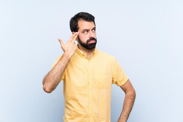 Junger mann mit bart über lokalisierter blauer wand mit den problemen, die selbstmord machen, gestikulieren