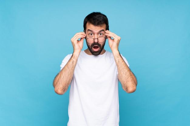 Junger mann mit bart über lokalisierter blauer wand mit gläsern und überrascht