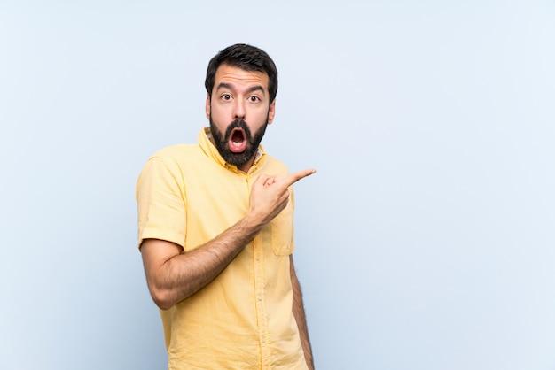 Junger mann mit bart über lokalisierter blauer wand überrascht und seite zeigend