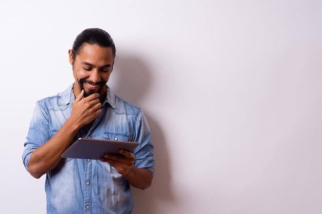 Junger mann mit bartgebundenem haar lächelt glücklich mit hand auf bart schaut auf seine tablette und lässt die rechte seite leer.