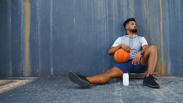 Junger mann mit basketball, der draußen in der stadt trainiert, sitzt und sich ausruht.