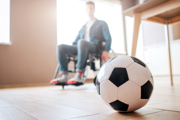 Junger mann mit behinderung sitzt auf rollstuhl und schaut auf ball für spiel herab. ex-sportler. verärgert und unglücklich. trauma. kann nicht mehr fußball spielen.