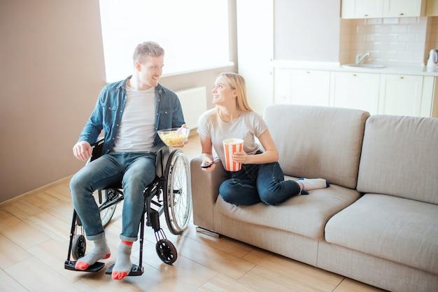 Junger mann mit behinderung sitzt neben frau auf sofa. sie sehen sich an und sile. film schauen. heimkino. liebe.