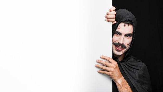 Junger mann mit blassem gesicht im schwarzen mantel, der im studio aufwirft