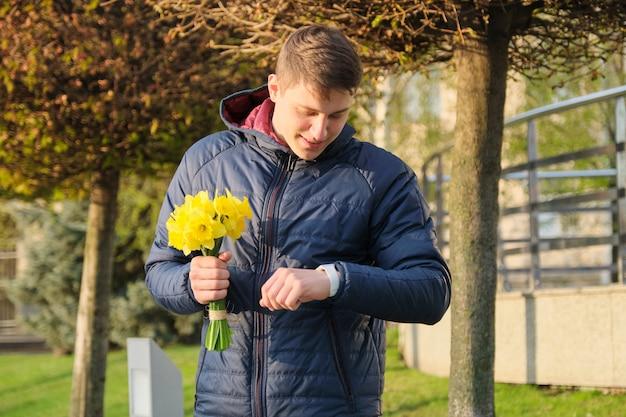 Junger mann mit blumenstrauß von frühlingsblumen betrachtet armbanduhr