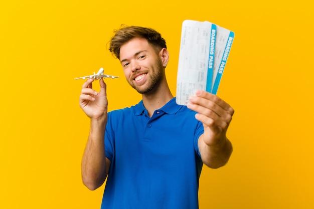 Junger mann mit bordkartekarten gegen orange
