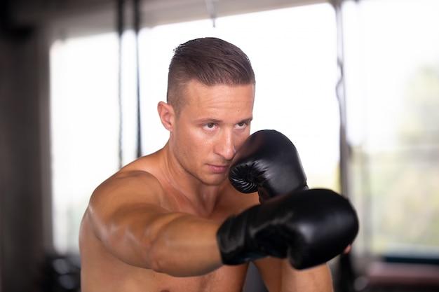 Junger mann mit boxhandschuhen, übung im fitnessstudio