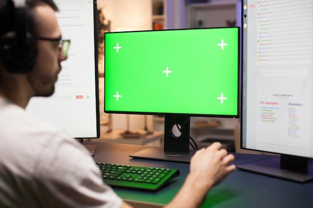 Junger mann mit brille, der beim streamen spiele auf dem computer mit grünem mock-up spielt.