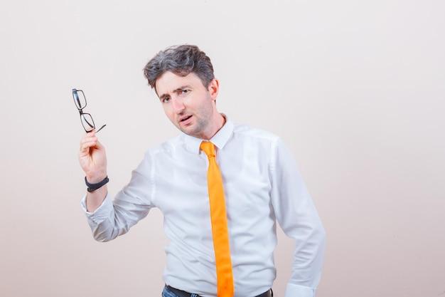 Junger mann mit brille in hemd, jeans und verwirrtem blick