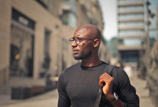 Junger mann mit brille trägt ein schwarzes t-shirt und einen rucksack auf der straße