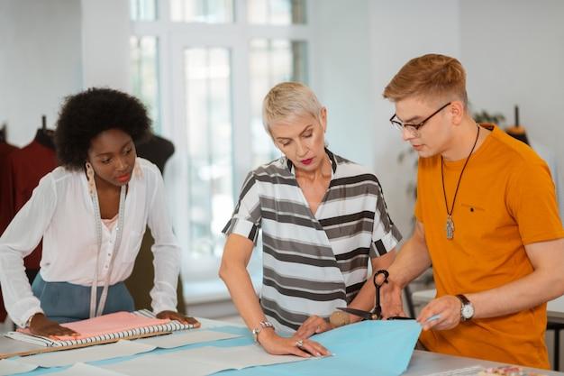 Junger mann mit brille und einem orangefarbenen t-shirt, das stoff mit einer schere in einem studio schneidet