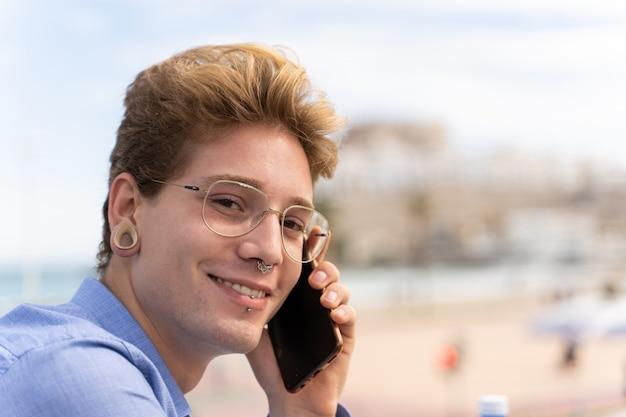 Junger mann mit brille und piercings im gespräch mit einem handy
