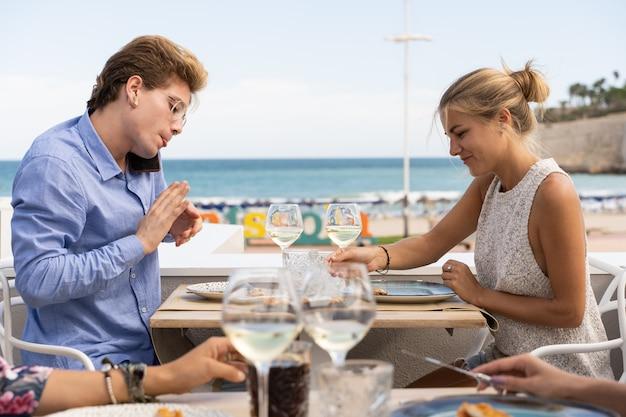 Junger mann mit brille und piercings sitzt auf einem tisch und spricht mit einem handy