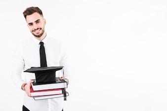 Junger Mann mit Büchern und Doktorhut