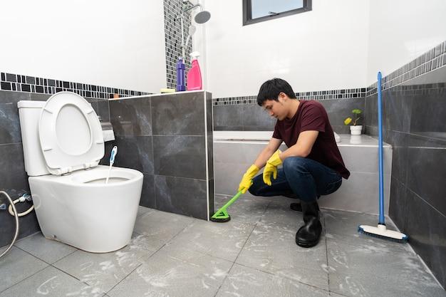 Junger mann mit bürste zum reinigen der fliese im badezimmer brush
