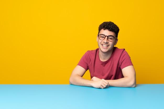 Junger mann mit bunter wand und tabelle mit gläsern und glücklichem