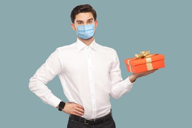 Junger mann mit chirurgischer medizinischer maske in weißem hemd, der mit der hand auf der taille steht und eine rote geschenkbox hält, mit zufriedenem gesicht in die kamera schaut. gesundheitskonzept. indoor, auf blauem hintergrund isoliert