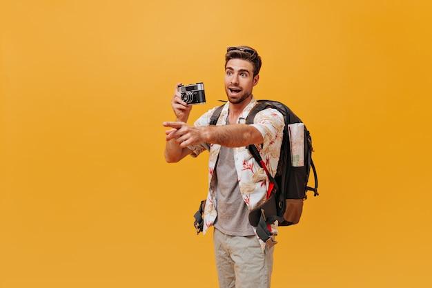 Junger mann mit cooler frisur und bart im stylischen sommerhemd posiert mit kamera und rucksack und zeigt seinen finger beiseite