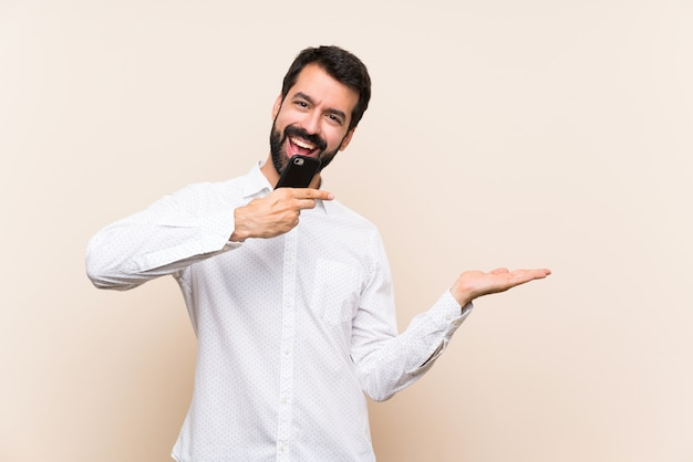 Junger mann mit dem bart, der ein bewegliches haltenes copyspace eingebildet auf der palme hält, um eine anzeige einzufügen