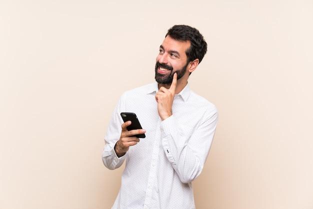 Junger mann mit dem bart, der ein mobile beim oben schauen denkt eine idee hält