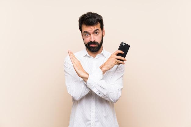 Junger mann mit dem bart, der ein mobile bildet keine geste anhält