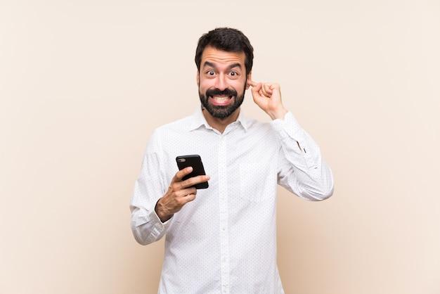 Junger mann mit dem bart, der ein mobile frustriert hält und ohren bedeckt