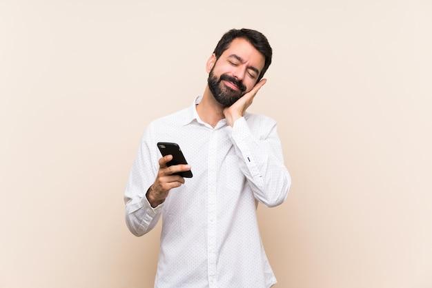Junger mann mit dem bart, der ein mobile hält, das schlafgeste im entzückenden ausdruck macht