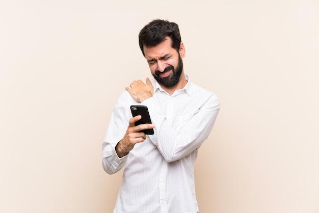 Junger mann mit dem bart, der ein mobile hält, das unter den schmerz in der schulter leidet, weil es sich bemüht hat