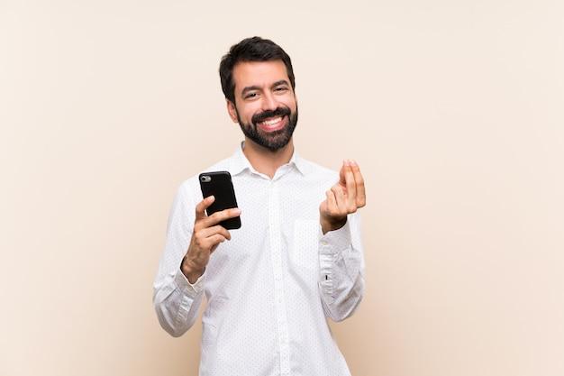 Junger mann mit dem bart, der ein mobile hält, geld zu verdienen, gestikulieren