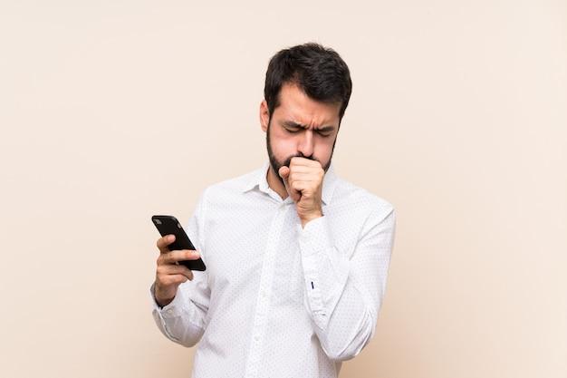 Junger mann mit dem bart, der ein mobile hält, leidet mit husten und dem gefühl schlecht