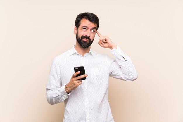 Junger mann mit dem bart, der ein mobile hat zweifel und das denken hält