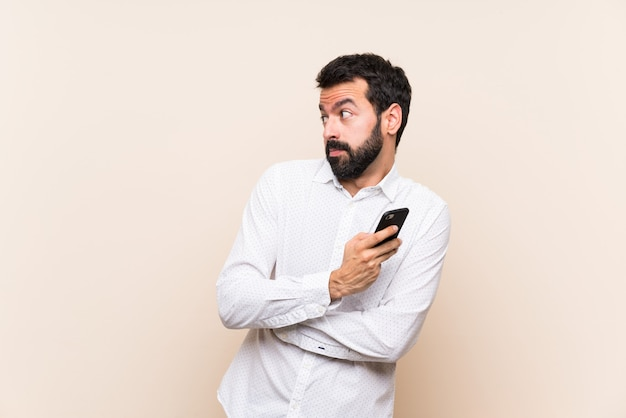 Junger mann mit dem bart, der ein mobile macht zweifel hält, gestikulieren beim anheben der schultern