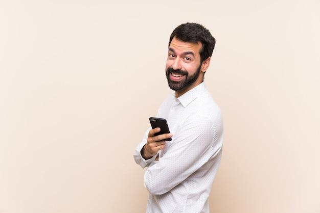 Junger mann mit dem bart, der ein mobile mit den armen gekreuzt hält und vorwärts schaut