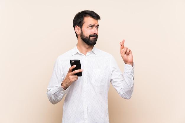 Junger mann mit dem bart, der ein mobile mit den fingern kreuzen und das beste wünschen hält