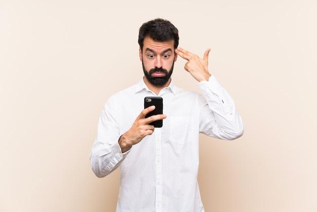 Junger mann mit dem bart, der ein mobile mit den problemen machen selbstmord hält, gestikulieren