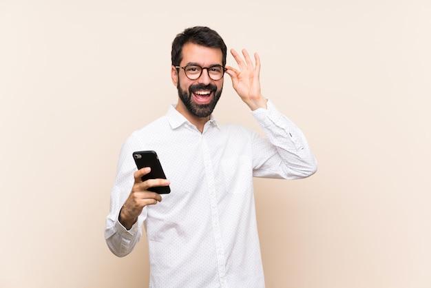 Junger mann mit dem bart, der ein mobile mit gläsern und glücklich hält