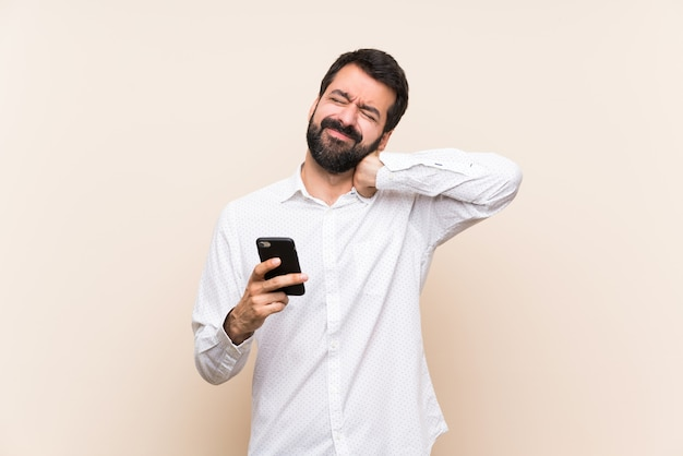 Junger mann mit dem bart, der ein mobile mit halsschmerzen hält