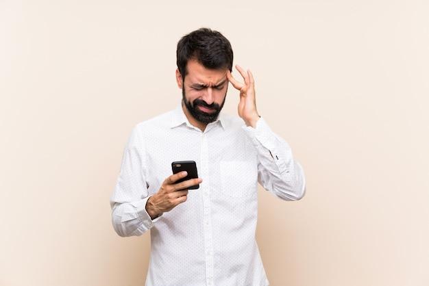 Junger mann mit dem bart, der ein mobile mit kopfschmerzen hält
